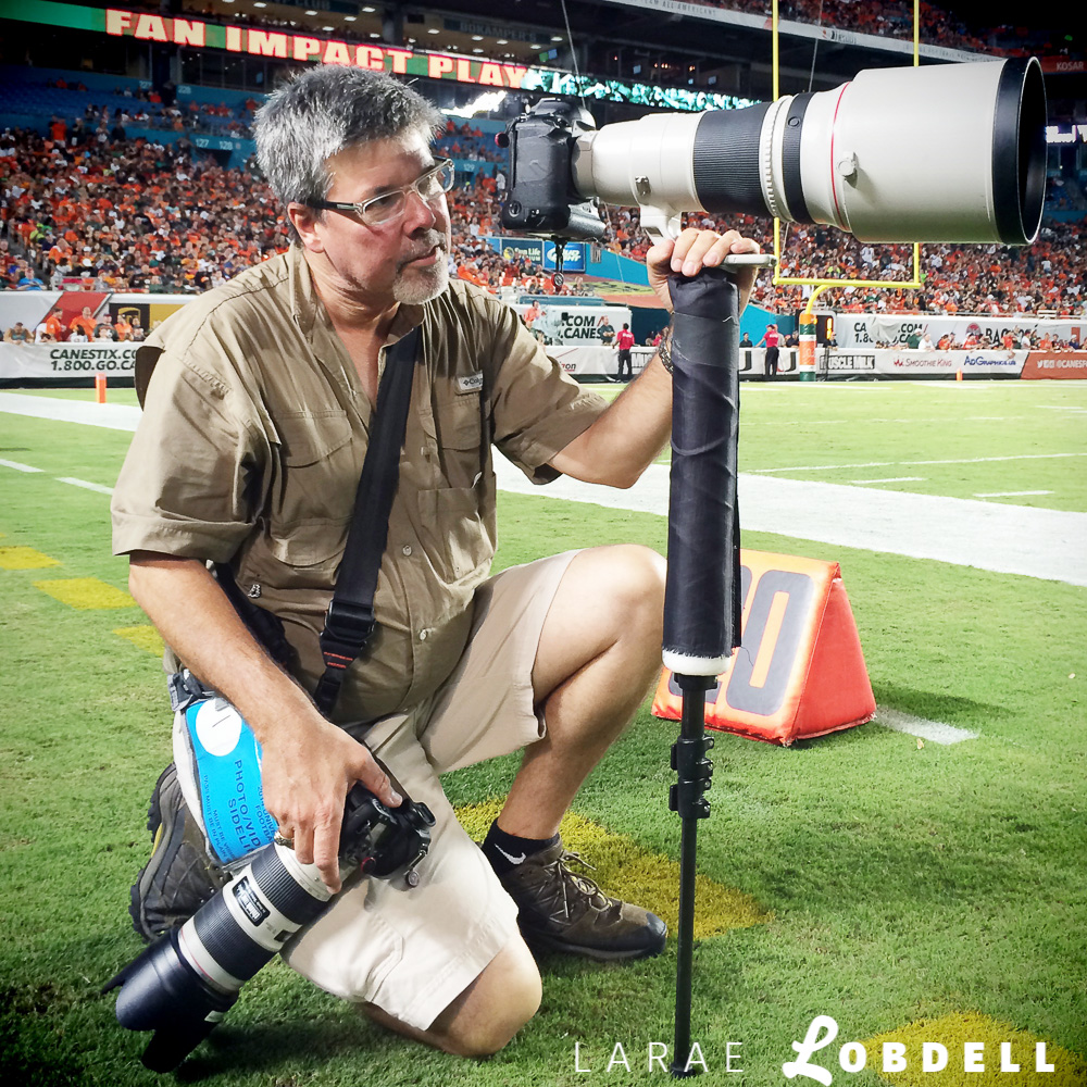 Miami Herald photographer, Al Diaz, looks for his next shot as the University of Miami hosts Florida A&M University at Sun Life Stadium in Miami Gardens on Saturday, September 6, 2014.