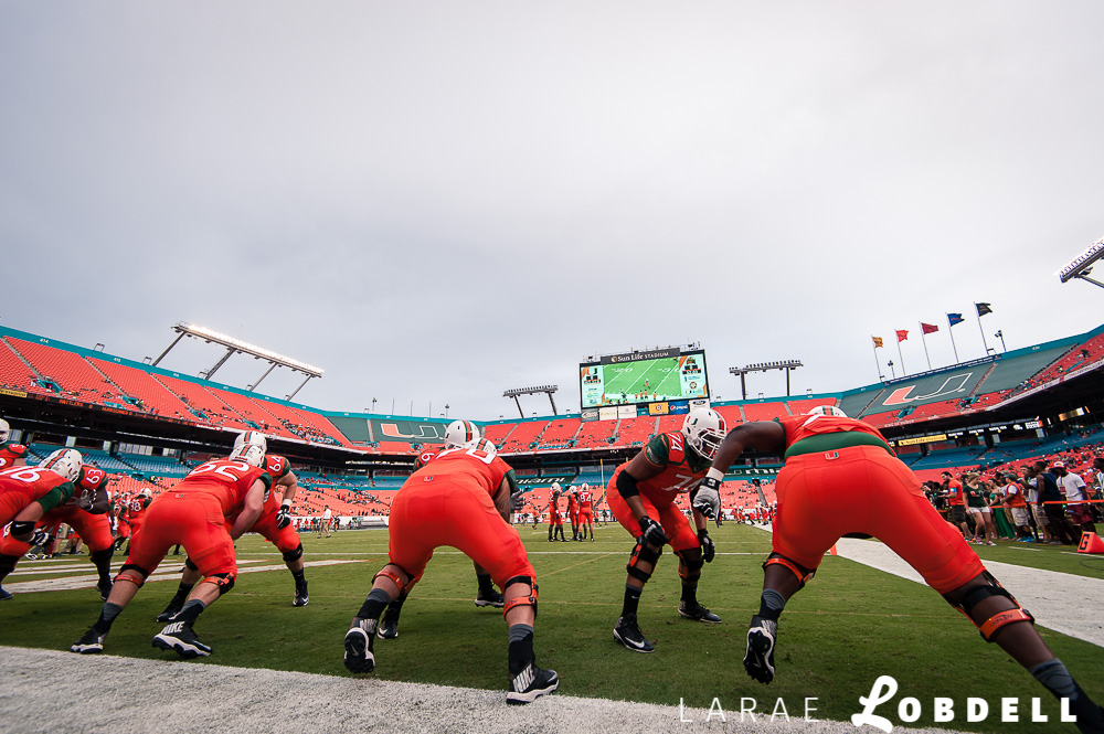 The team warm up on the field as the University of Miami hosts Florida A&M University at Sun Life Stadium in Miami Gardens on Saturday, September 6, 2014. © LaRae Lobdell |Camera: Nikon D700 with 16-35/4.0 lens