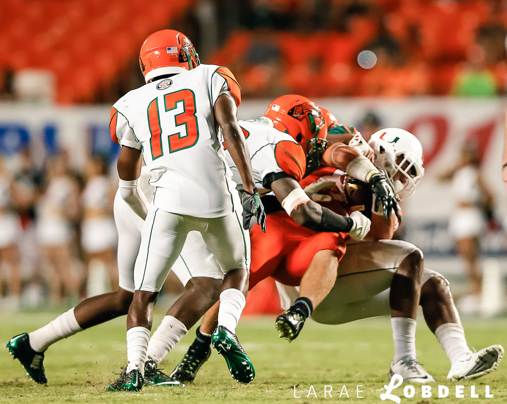 University of Miami Hurricanes wide receiver Braxton Berrios (83) is taken down in the fourth quarter as the University of Miami hosts Florida A&M University at Sun Life Stadium in Miami Gardens on Saturday, September 6, 2014. © LaRae Lobdell Camera: Canon 400/2.8 on an EOS-1D X