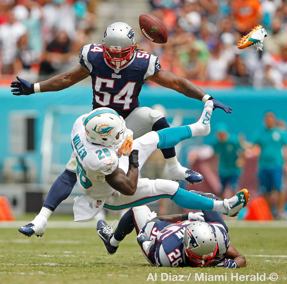 Miami Dolphins running back Lamar Miller (26) fumbles and loses his shoe after getting hit by the Patriots Logan Ryan in the second quarter as the Miami Dolphins host the New England Patriots at Sun Life Stadium in Miami Gardens on Sunday, September 7, 2014.© Al Diaz / Miami Herald